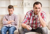 image of boring  - Boy sitting at sofa and get bored while his father watching television - JPG
