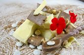 image of sprinkling  - Black and white chocolate cubes on a cocoa sprinkled table decorated with flowers and a chocolate spoon