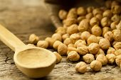 stock photo of chickpea  - scattered chickpeas from a jute bag with a spoon on old wooden background  - JPG