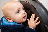 image of fascinating  - Portrait of a cute little baby boy looking with fascination inside the washing machine  - JPG