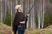 picture of hunter  - Woman hunter with gun in spring forest - JPG