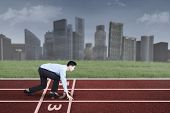 foto of competing  - Young entrepreneur in ready position to run and compete for success - JPG
