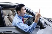picture of middle finger  - Young man driving a car and looks angry screaming and showing middle finger - JPG