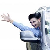 stock photo of waving hands  - Portrait of cheerful young man looks happy while driving a car and waving hand - JPG