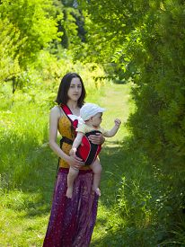 picture of sling bag  - Young mother walking in the Park and holding a small child in a Baby Carrier bag. ** Note: Soft Focus at 100%, best at smaller sizes - JPG