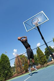 picture of slam  - Young basketball player driving to the hoop for a high flying slam dunk - JPG