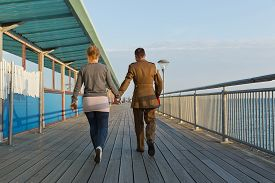 picture of girl walking away  - A girl in a track suit and a guy in his army suit walking away from the camera walking at the pier at sunset hour on a summer day with no clouds in the sky