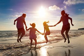 image of children beach  - happy family jumping together on the beach - JPG
