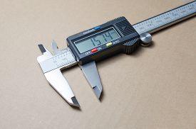 stock photo of vernier-caliper  - Digital electronic vernier caliper on a brown background - JPG