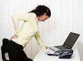 pic of spinal disc  - Woman with back pain of the intervertebral disc in office - JPG