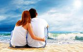 foto of couple sitting beach  - Sea view of a couple sitting on beach - JPG