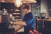 Handsome barista preparing cup of coffee for customer in coffee shop. poster