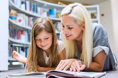 Постер, плакат: Mother With Daughter Read Book Together In Library