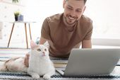 Young Man With Cute Cat And Laptop At Home poster