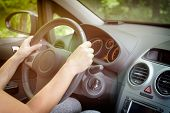 Woman driving a car, close up of her hand at the steering wheel. View from behind poster