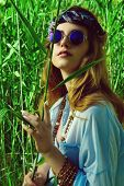Beautiful hippie girl stands among the reeds in a summer sunny day. Spirit of freedom. Fashion shot. poster