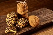 Sweet Assortment Of Biscuits On A Round Wood Log Over Rustic Wooden Background, Close-up, Selective  poster