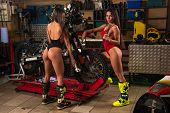 Sexy Biker Girl In Red Lingerie Posing With Sport Motorcycle In Garage poster