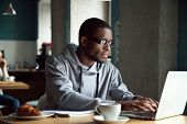 Serious Millennial African-american Man Using Laptop Sitting At Cafe Table, Focused Black Casual Guy poster