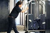 Closeup Many Suitcases On Hotel Luggage Cart Moving By Bell Boy. Baggage Porter Or Bell Boy Bringing poster