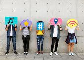 Teenagers covering their faces with social media icons poster