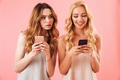Two young pretty women in pajamas using smartphones while brunette woman looks at smartphone her fri poster
