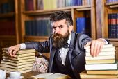 Man Sits At Table With Many Books. Mature Man Has Serious Face And Looks Confident. Successful Study poster