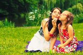 Mother And Little Girl Daughter Child Blowing Soap Bubbles Outdoor. Parent And Kid Having Fun In Par poster
