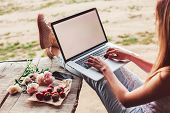 Young Woman Using And Typing Laptop Computer At Rough Wooden Table With Coffee Cup, Strawberries, Bo poster