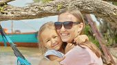 Portrait Of Young Happy Mother Having Fun With Her Little Cute Daughter On Hammock At The Sandy Beac poster