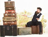 Macho Elegant On Surprised Face Sits Shocked Near Pile Of Vintage Suitcase. Luggage And Travelling C poster