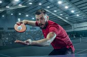 The Table Tennis Player In Motion. Fit Young Sports Man Tennis-player In Play On Sport Arena Backgro poster