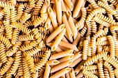 Variety Of Types And Shapes Of Dry Italian Pasta - Fusilli And Penne, Top View. Uncooked Whole Wheat poster