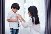 Young Asian Mom Dressed Up Son Outfits For Preparing Go To School. Mother And Son Concept. Happy Fam poster