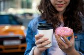 Hands Holding A Pink Donut And Coffee On The Background Of A Busy Metropolis. poster