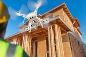 Pilot Flies Drone Quadcopter Inspecting Home Construction Site. poster