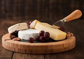 Selection Of Various Cheese On The Board And Grapes On Wooden Table Background. Blue Stilton, Red Le poster