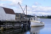 stock photo of lobster boat  - A small work boat is moored to a wooden wharf loaded with lobster pots - JPG