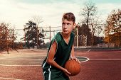 Sports And Basketball. A Young Teenager In A Green Tracksuit Poses With A Basketball In His Hands An poster
