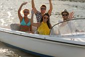 Waving young people in sunglasses sitting in motorboat summertime