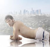 Beautiful male model wrapped in towel laying down against scenic city view background