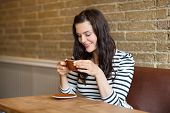 Beautiful young woman smiling while drinking coffee in cafeteria