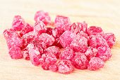 foto of uncut  - A pile of raw uncut ruby crystals on wood - JPG