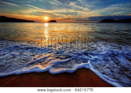 Colorful seaside beach sunrise with distant mountains poster