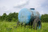 picture of cistern  - Blue water cistern for animal stand between pasture grass and clovers move in wind. ** Note: Soft Focus at 100%, best at smaller sizes - JPG