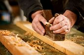 pic of joinery  - Skilled carpenter using a handheld plane to smooth and level the surface of a plank of hardwood close up view of his hands the tool and wood shavings  - JPG