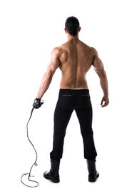 pic of strip tease  - Back of muscular shirtless young man with whip and studded glove on white background full body shot - JPG