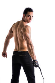 stock photo of strip tease  - Muscular shirtless young man with whip and studded glove on white background from the back - JPG