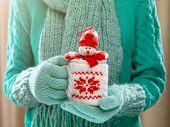 stock photo of sneak  - Little toy snowman in a winter cup in female hands - JPG