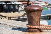 image of bollard  - old bollard with rope mooring and boats in the background